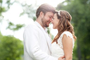 bride and groom kiss under a tree