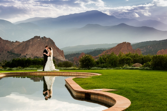 bride and groom kiis in front of mountains