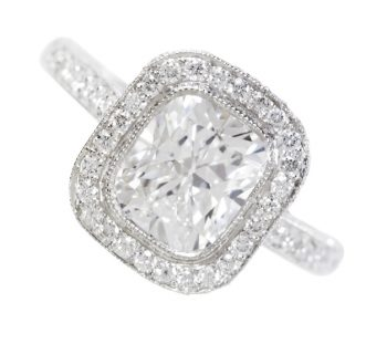 Rounded square diamond ring with diamond encrusted band, close-up.