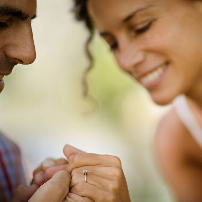 Man holding womands hand and looking at diamond engagement ring