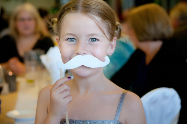 little girl at a wedding with a paper moustache