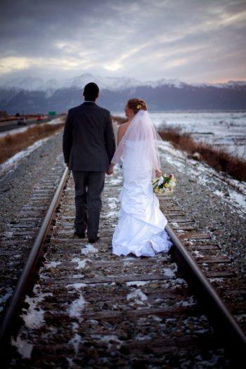 snowy alaska bride and groom walk on railroad tracks