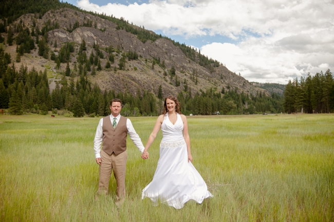 bride and groom hold hands in a meadow