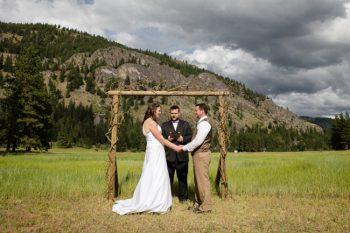 bride and grom marry under a handmade arbor