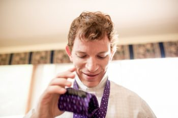 groom tying purple tie