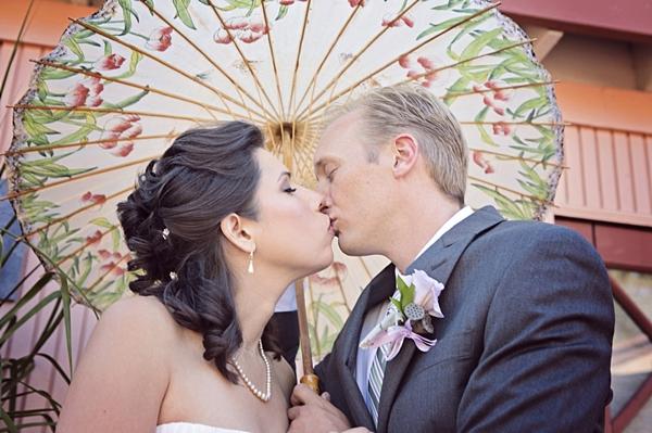 bride and groom kiss under a paper umbrella
