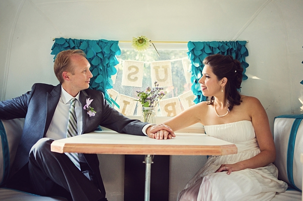 bride and groom in a vintage camper