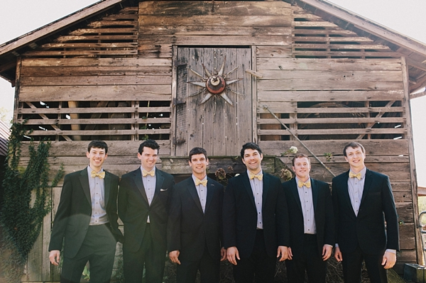 groomsmen in bow ties at rustic barn