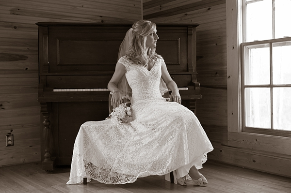 bride sits at a vintage chuch piano and looks out a window
