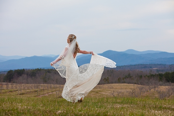 Bride dancing on a  hilltop with smoky mountains in the distance