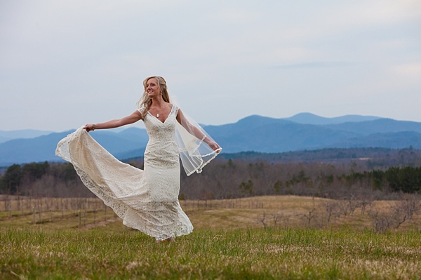 Bride twirling on a  hilltop with smoky mountains in the distance