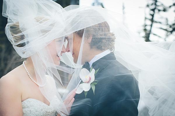bride and groom behind bride's tulle veil