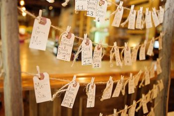 escort cards hanging from a vintage wooden window frame