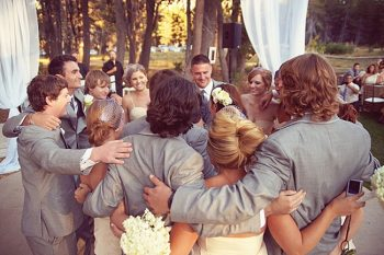 friends gather around bride and groom on the dance floor