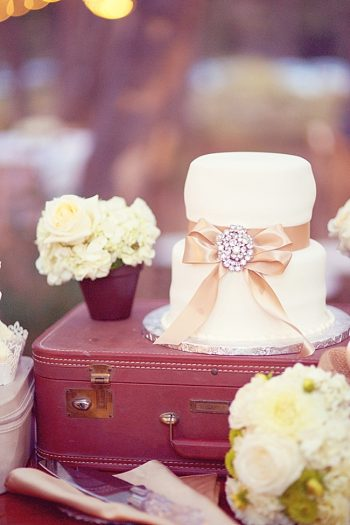 mini wedding cake with ribbon and brooch
