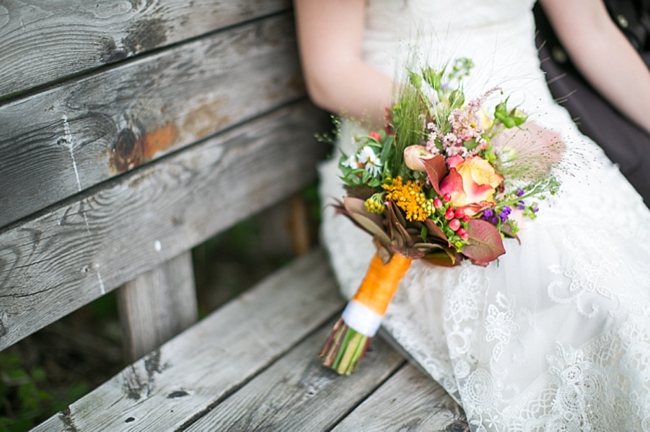 bride on wooden bench with mountain wild flower inspired bouquet
