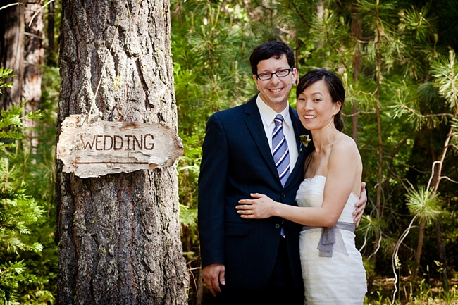 Bride and groom at wooden wedding sign in Yosemite National Park