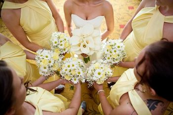 bridesmaids in yellow dresses and yellow and white daisy bouquets