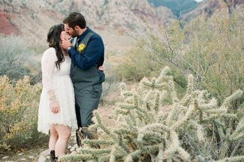 bride and groom stand near a cholla bush photo by Gaby J Photography