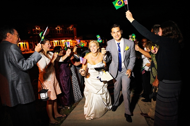 bride and groom exit while guests wave American and Brazilian Flags