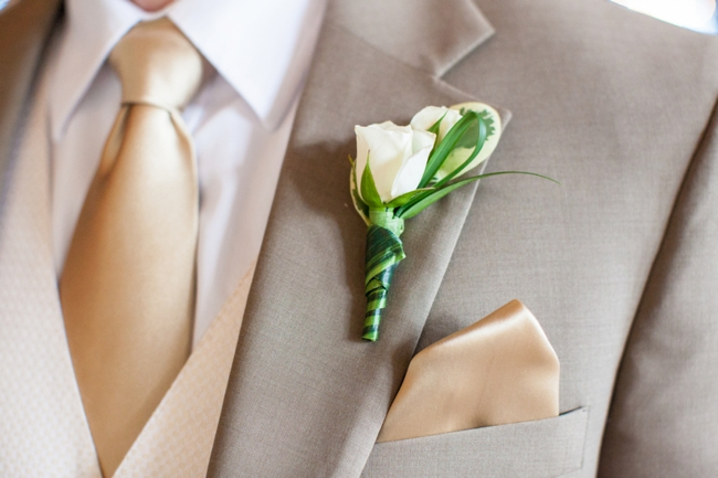 tan suite, golden tie, and white rose boutonniere