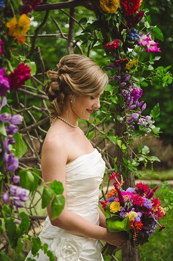 bride at floral ceremony arch via https://mountainsidebride.com