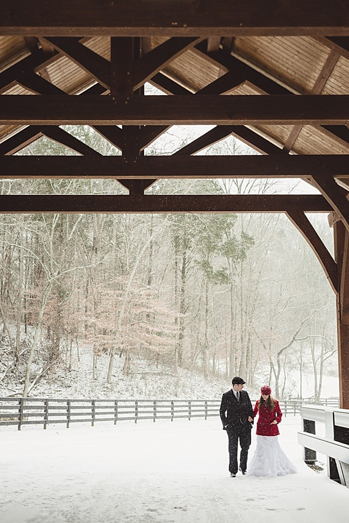 bride and groom under covered bridge