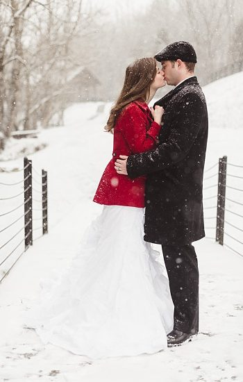bride in red coat with groom on a bridge