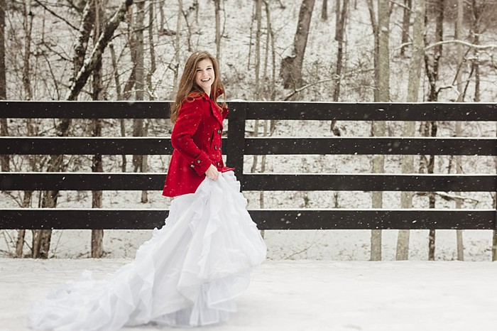 bride in red coat on a bridge