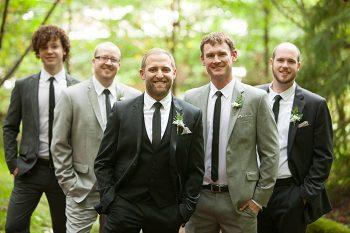 groomsmen in suits in woods