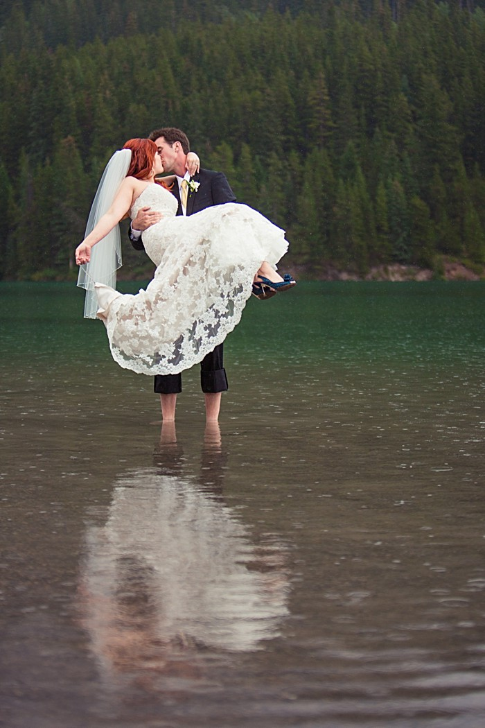 groom holds his bride in a river| Banff Wedding by Just for You Photography