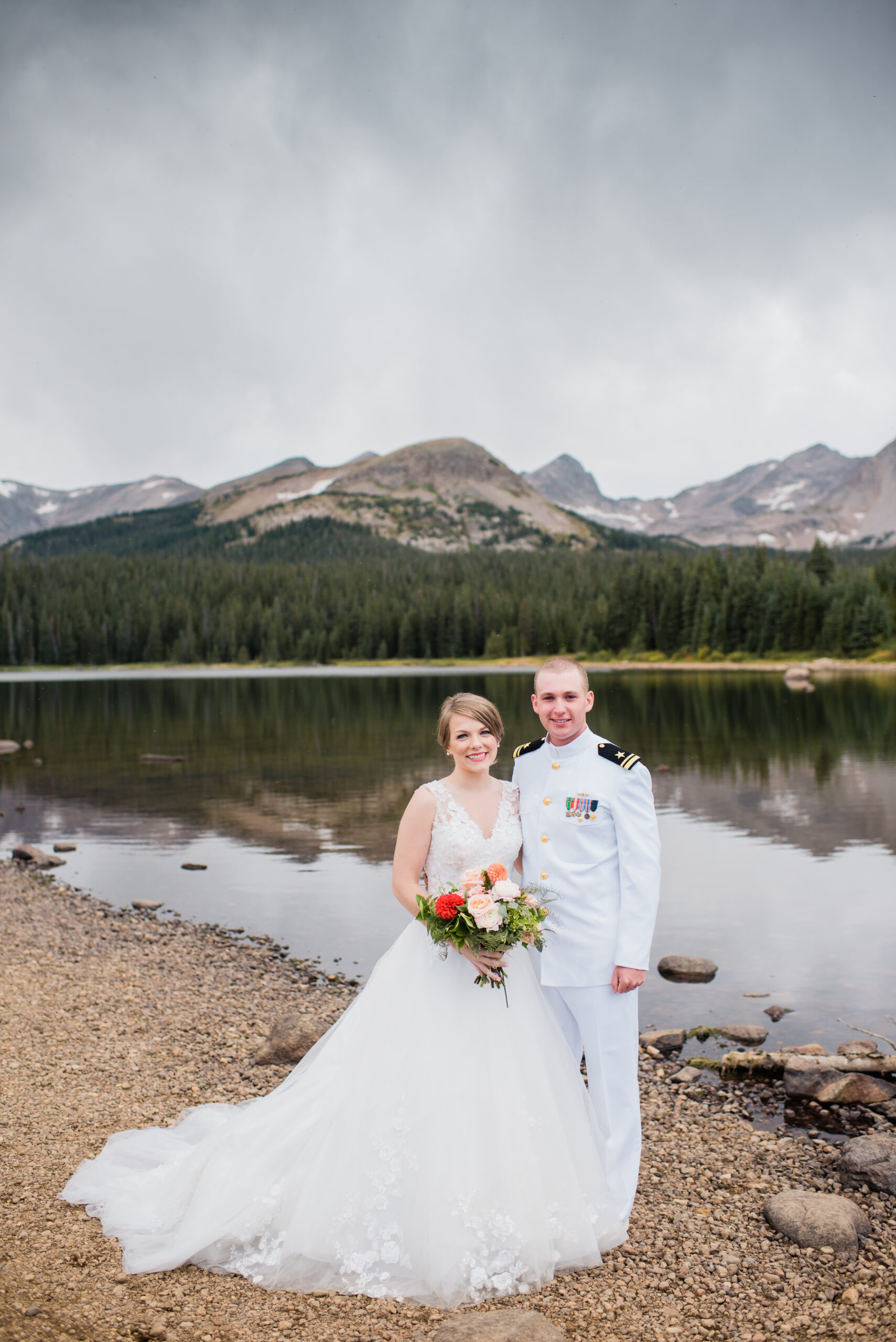 bride and groom by the lake with mountains in the background