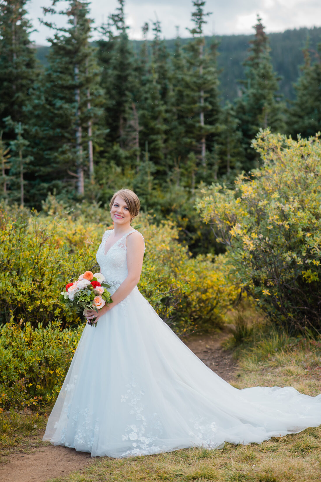bride in lace wedding gown by the lake