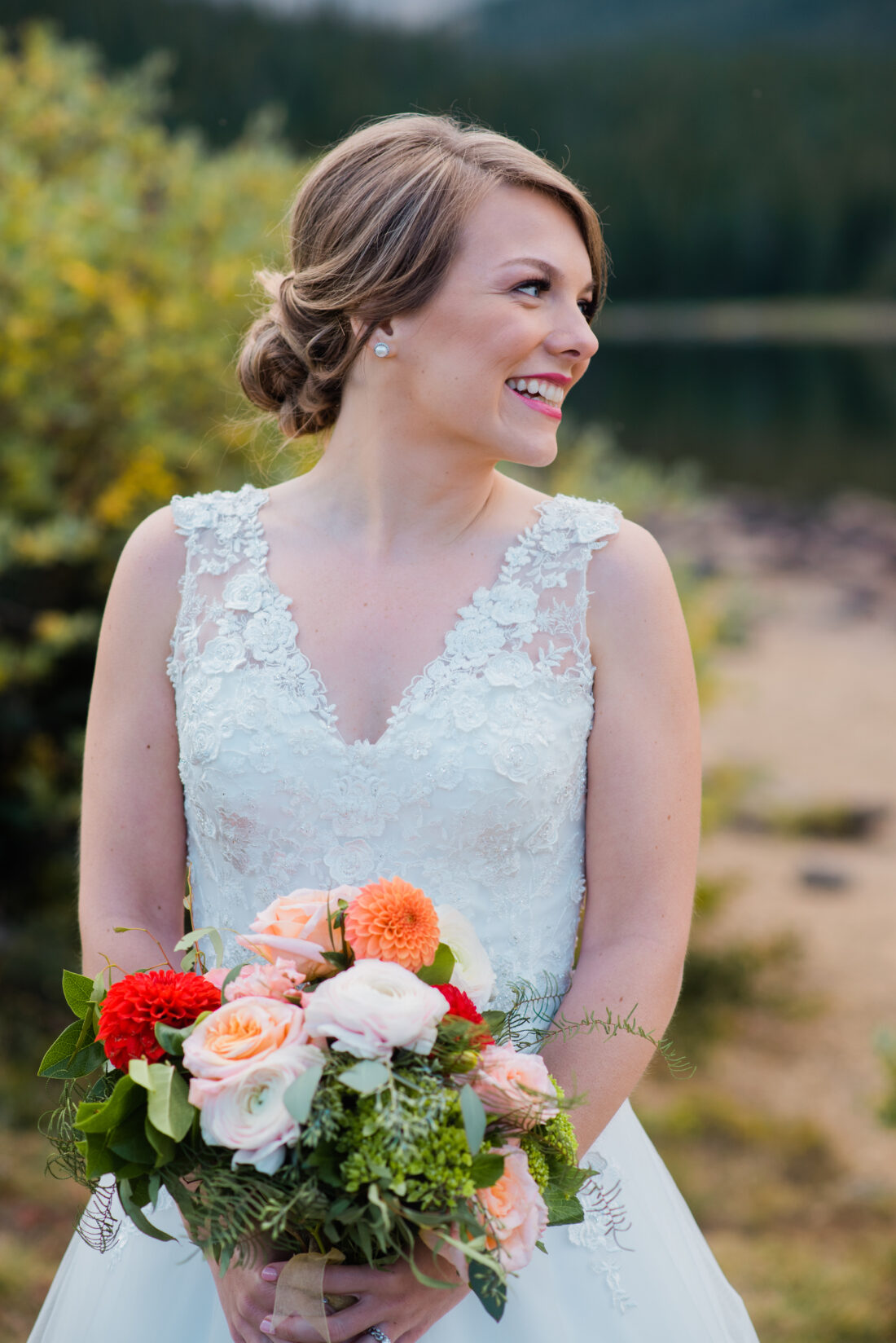 bride in lace wedding gown by the lake holding flowers