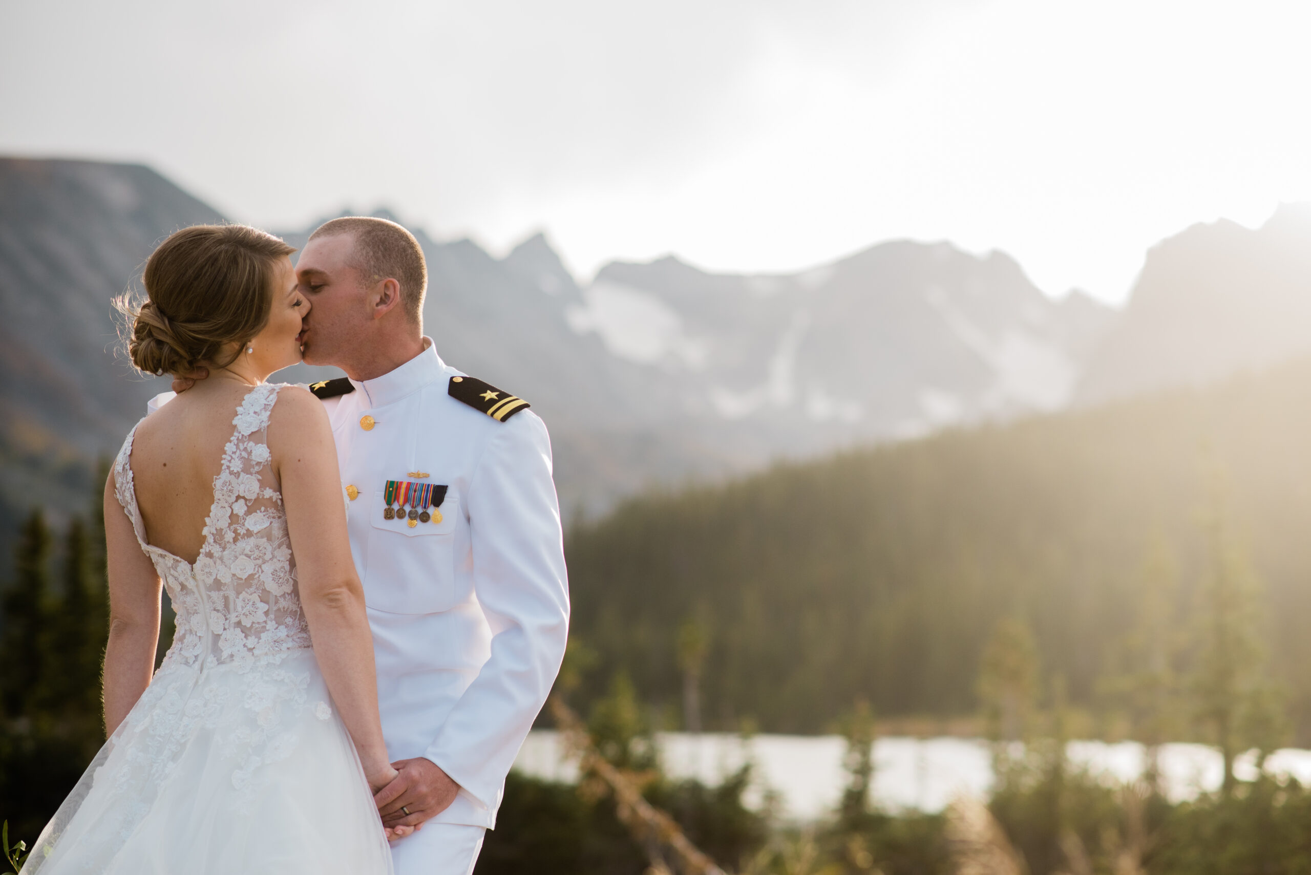 bride and groom standing by lake with mountains in the background
