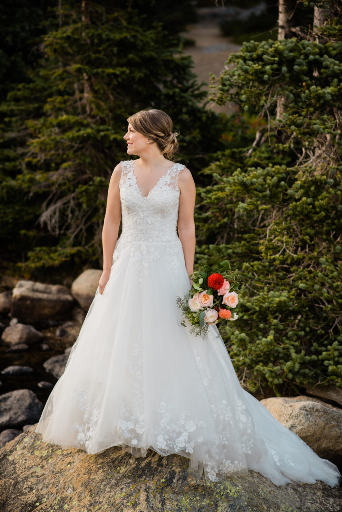bride standing by lake with mountains in the background