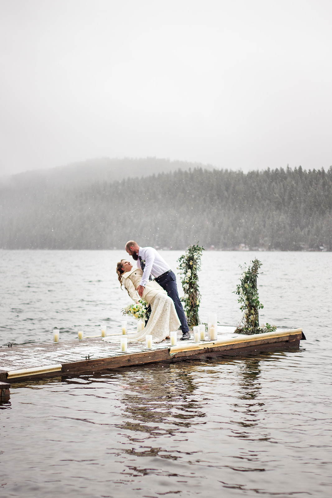 bride and groom on lake dock with mountains in the background